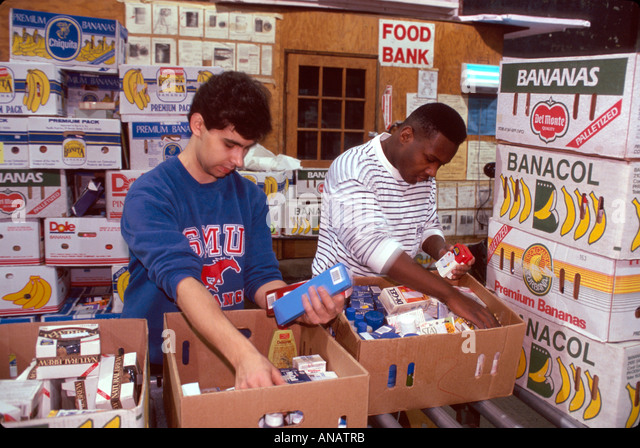 New Jersey Hoboken Food Bank volunteers sort donations Black male students community service - Stock Image