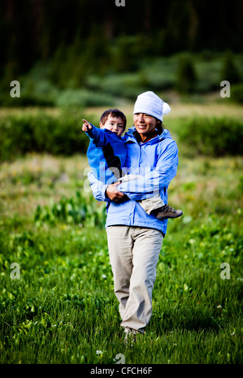 A woman walks through a meadow at Squaw Pass holding her 2 year old son. - Stock Image