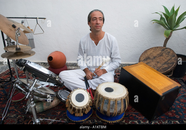 musician sits surrounded by his percussion instruments - Stock-Bilder
