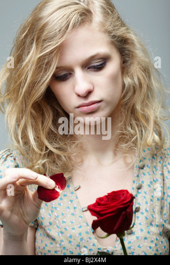 Woman pulling the petals off a rose - Stock Image