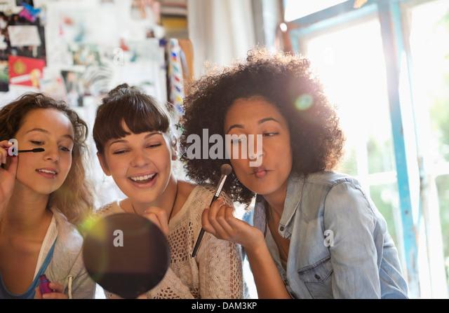 Women applying makeup in bedroom - Stock Image