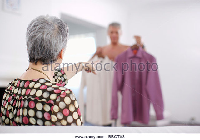 Senior woman pointing at shirts that man is deciding between - Stock Image