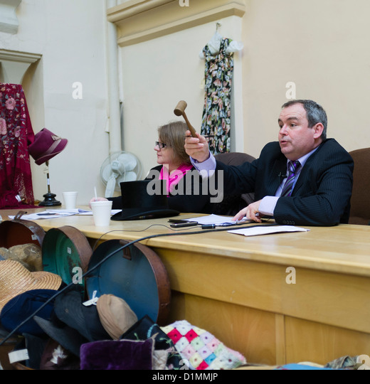 An auctioneer holding his gavel taking bids at an auction of antiques, clothes and bric-a-brac, UK - Stock Image