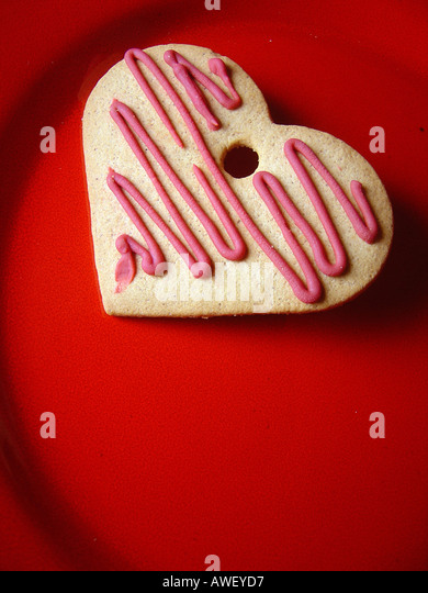 Still Life of a Valentine s Day Heart Shaped Cookie Biscuit on a Red Plate Viewed From Above Copy Space - Stock Image