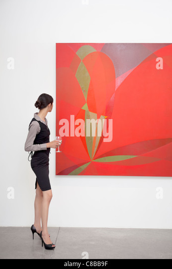 Full length of a woman looking at painting in art gallery - Stock Image