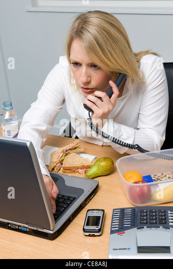 female office worker eating working lunch - Stock Image