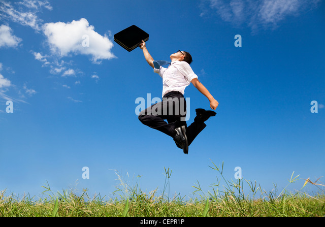 happy and successful businessman jumping on the field - Stock Image