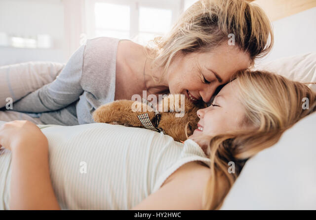 Cute little girl lying on bed with her mother. Mother and daughter sleeping together at home. - Stock Image