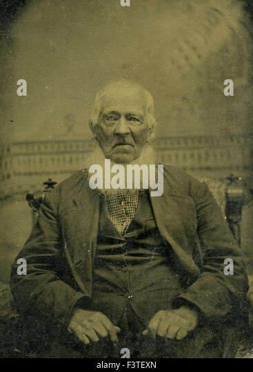 Older man with a white beard in suit seated in chair during a photo sitting that produced a tin-type photograph - Stock-Bilder