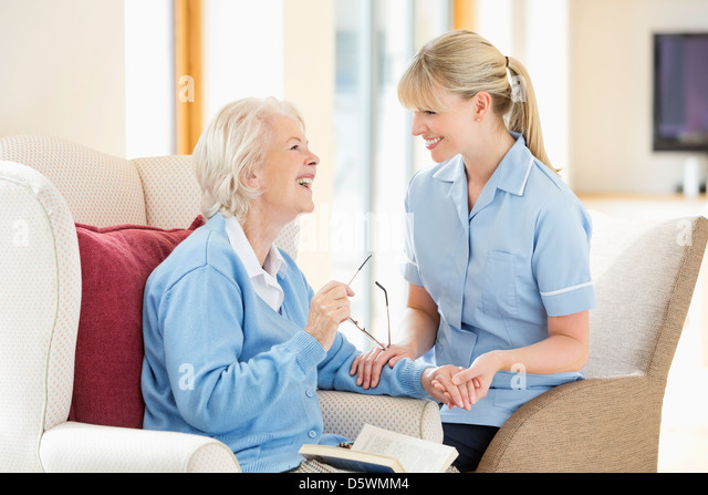 Caregiver talking with older woman - Stock Image