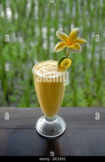 Soft drink, mango smoothie in a glass decorated with flowers, in front of a rice field in Ubud, Bali, Indonesia, - Stock Image