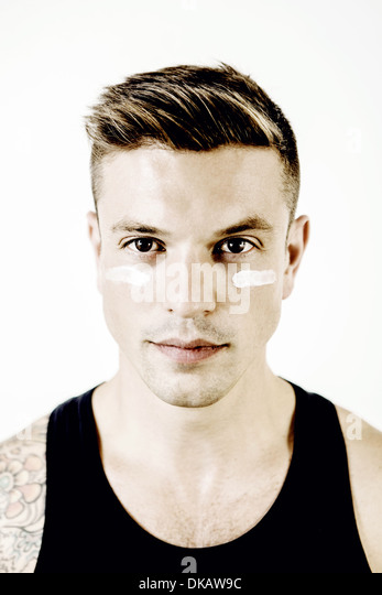 Portrait of mid adult man with makeup under eyes - Stock Image