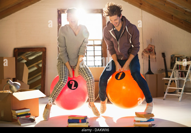 Couple jumping on exercise balls together - Stock Image