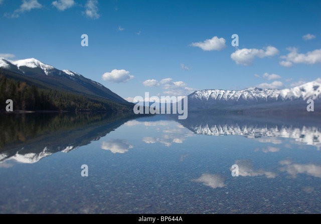Snow capped mountains and sky reflected in water - Stock-Bilder