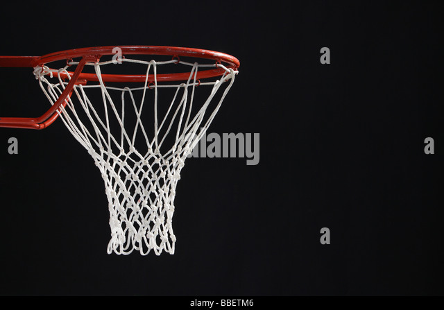 Empty basketball hoop against black background - Stock Image
