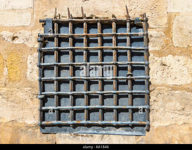 Old metal grating in stone wall - France. - Stock Image