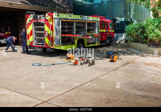Two firemen check equipment. London Fire Brigade, Euston Road Station, England, British, Britain, UK, emergency - Stock Image