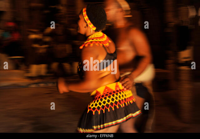 Female dancer in colourful beaded dress with male performer in traditional dance show at Shakaland KwaZulu-Natal - Stock-Bilder