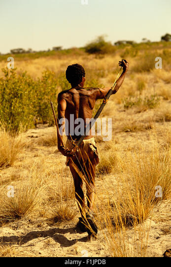 Bushman Walking Through Kalahari Desert, Botswana, Africa - Stock Image
