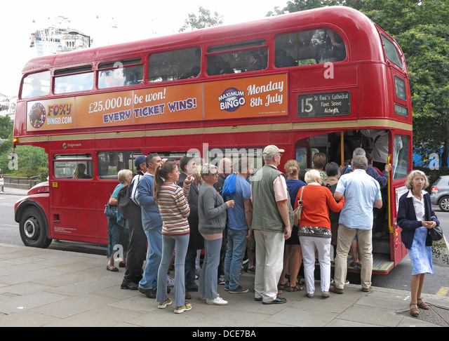 A group of tourists queuing to board a red London Routemaster bus , Great Britain - Stock Image