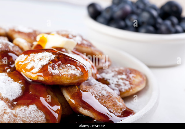 Dutch mini pancakes, or poffertjes, with butter, syrup and powdered sugar. Fresh blueberries out of focus in the - Stock Image