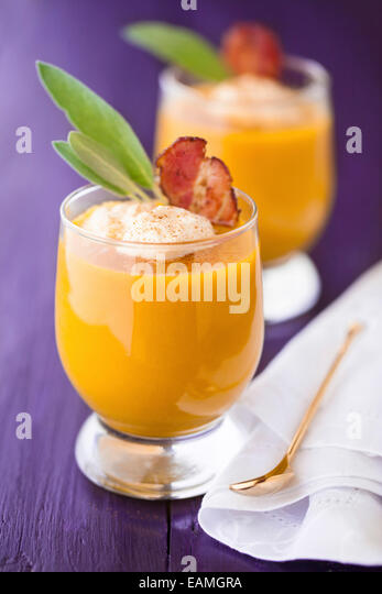 Pumpkin soup served in glasses with whipped cream, bacon and sage - Stock Image