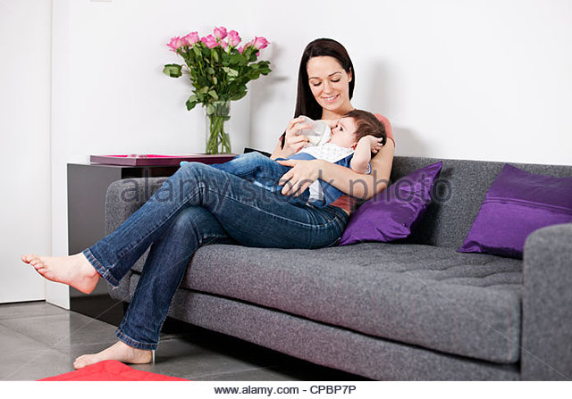 A mother feeding her baby son a bottle of milk - Stock Image