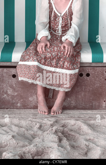 a girl with a floral dress is sitting in a beach chair - Stock Image