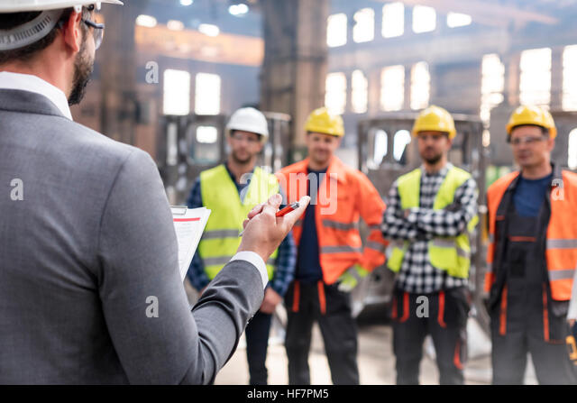 Steel workers listening to manager in meeting in factory - Stock Image