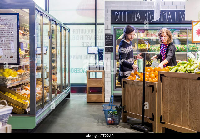 Young woman and man buying oranges in supermarket - Stock-Bilder