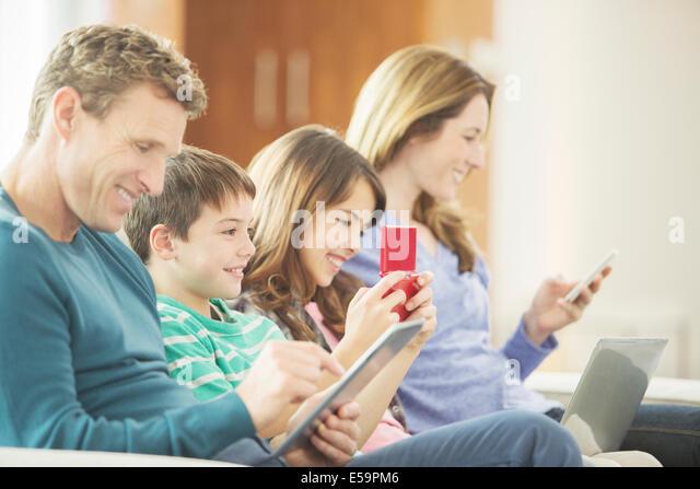 Family using technology on sofa - Stock Image