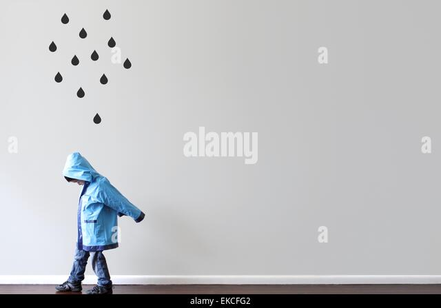 Boy walking past a wall with black raindrops painted on the wall - Stock-Bilder