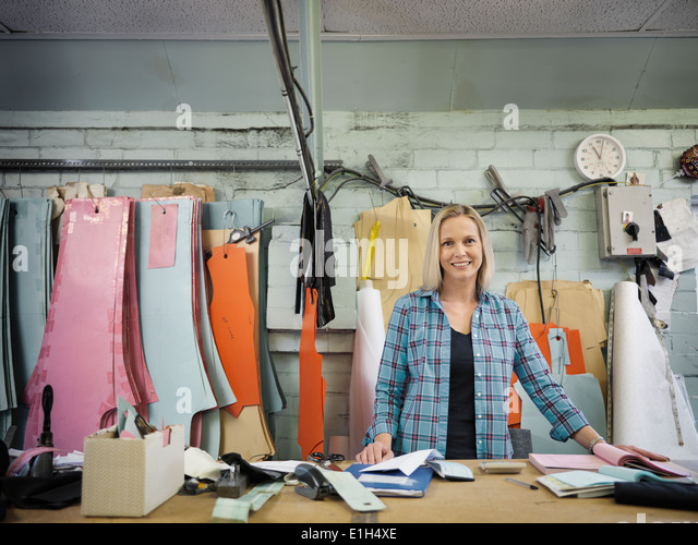 Portrait of fashion designer at cutting desk in clothing factory, smiling - Stock Image