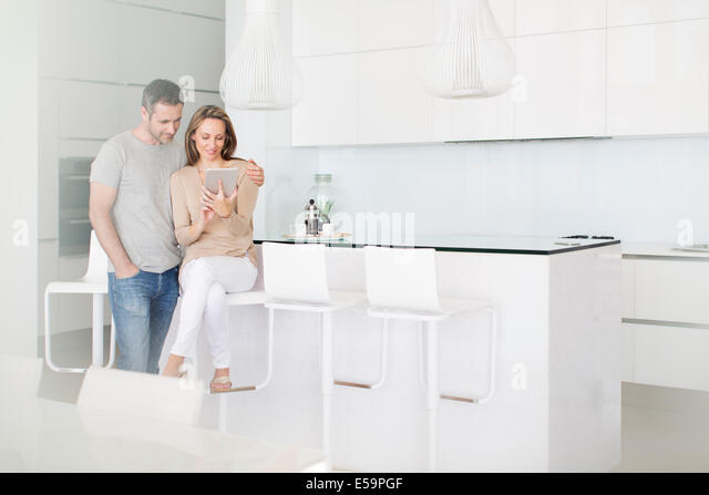 Couple using digital tablet in kitchen - Stock Image