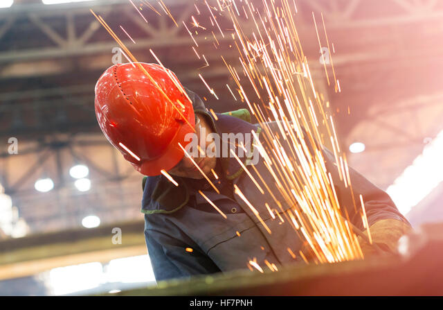 Welder using welding torch with sparks in steel factory - Stock Image