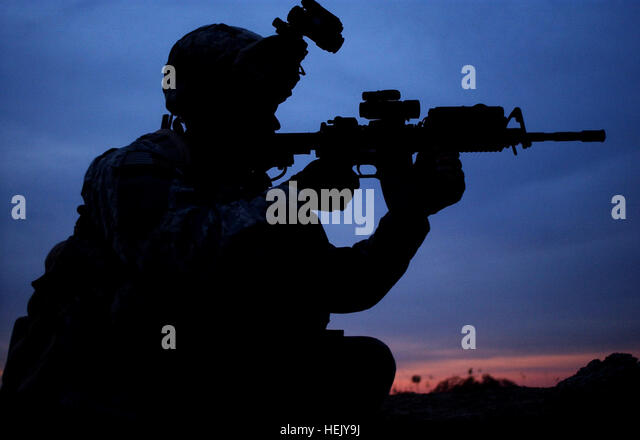 U.S. Army Spc. Dean Goble checks through his rifle scope for any suspicious activity at an observation point in - Stock Image