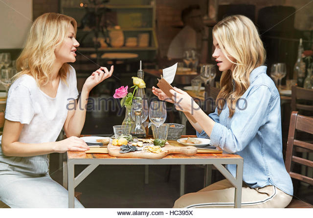 Friends sitting together at cafe. - Stock Image