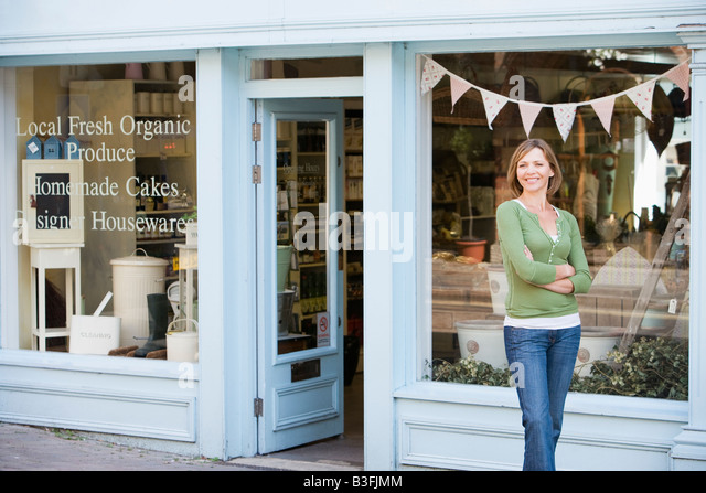 Woman standing in front of organic food store smiling - Stock Image
