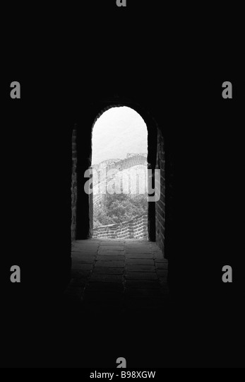 Looking down dark passageway to open arched doorway of room perched atop Great Wall of China - Stock Image