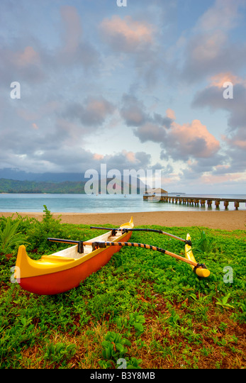 Sunrise with pier and canoe at Hanalei Bay Kauai Hawaii - Stock Image