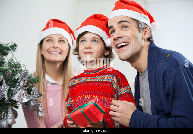 Happy Family With Christmas Gift Looking Away - Stock Image