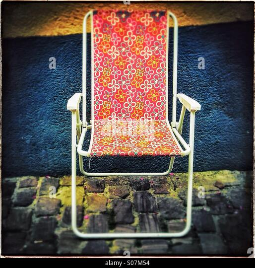 Empty plastic beach chair sitting alone on cobbled street in Alsace, France - Stock Image