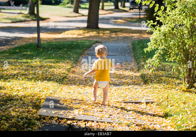 Boy walking along sidewalk, Michigan, America, USA - Stock Image