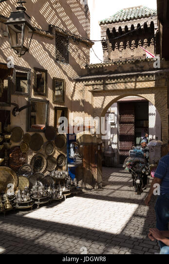 Brass and metal trays, teapots and other fancy goods on the street outside a small shop in Fez, Morocco. A man guides - Stock Image