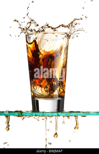 Ice cube dropped into a soda creating a splash - Stock Image