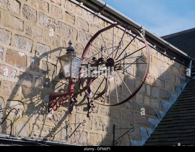 Old rusty wheel on the wall out side a pub in Holbrook near Belper, Derbyshire, United Kingdom, UK - Stock Image
