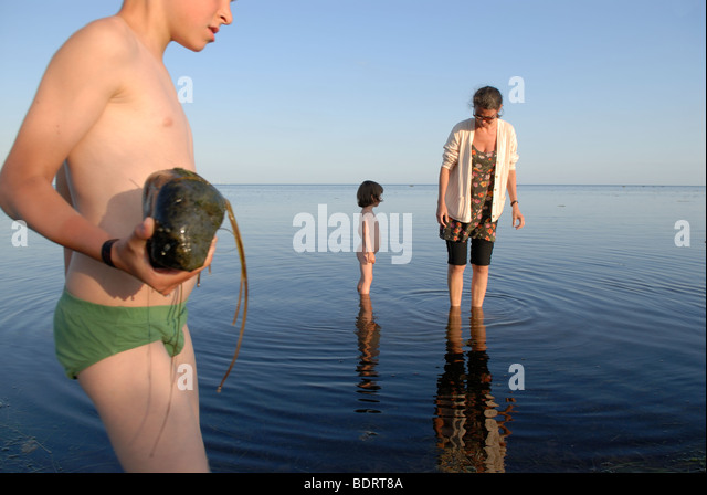 MOTHER WITH TWO CHILDREN IN THE WATER - Stock Image