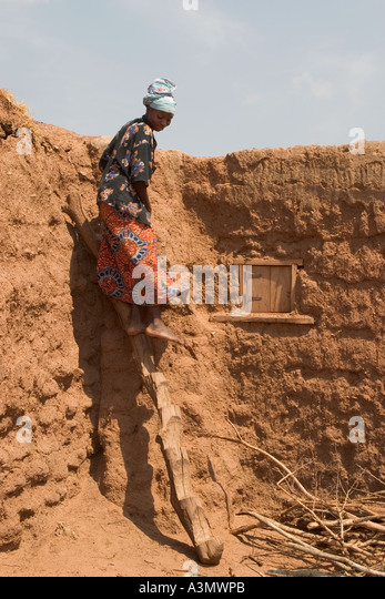 Village woman, Larabanga, Ghana, using ridgid ladder made from tree trunk to get down from her house roof. - Stock Image