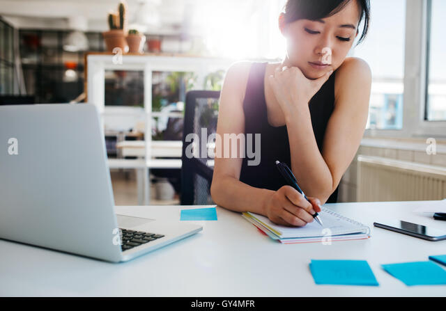 Shot of asian businesswoman writing notes on notepad. Female executive sitting at her desk with laptop taking notes. - Stock Image