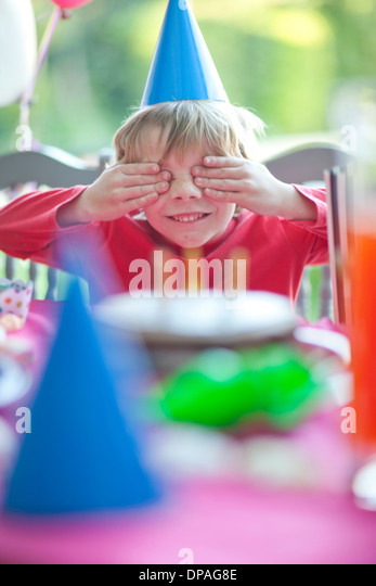 Young boy with hands over eyes at birthday party - Stock Image